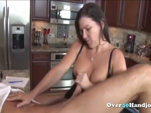 busty milf jerking his cock in kitchen